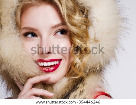 Fashion photo of a beautiful blond model with red lips, in fur hood