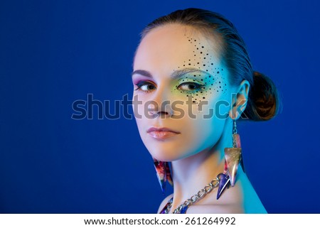 Fashion photo of a beautiful with bright makeup and jewelry - stock photo