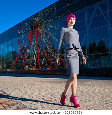 Fashion photo of a beautiful woman in front of a building with reflection of Ferris wheel at summer time - stock photo