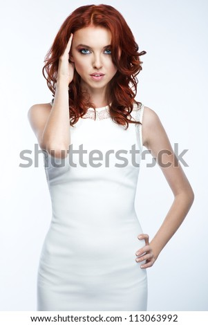 Fashion photo of a young woman with curly red hair wearing white dress