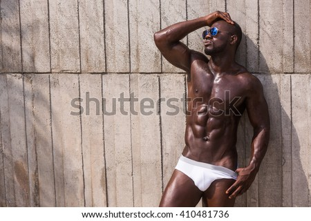 Fashion photo of african american athletic man with sport wet body posing near texture wall topless - stock photo