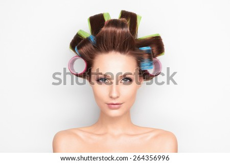 fashion photo of beautiful brunette woman with curler in the hair. Beauty hairstyle girl - stock photo