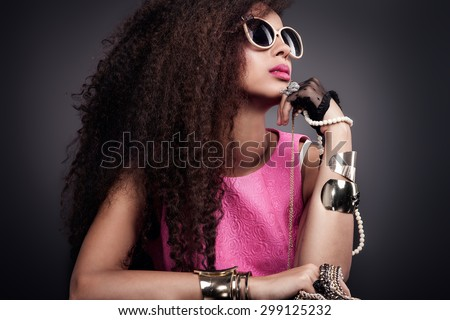 Fashion photo of beautiful elegant african american woman. Girl posing with a lot of jewelry, wearing fashionable sunglasses. Girl with long curly healthy hair. Beauty portrait. Studio shot.  - stock photo
