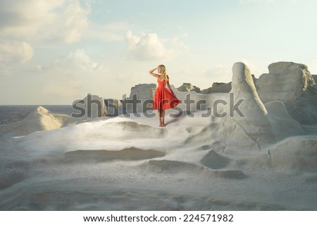Fashion photo of beautiful lady in red dress in an unusual landscape - stock photo