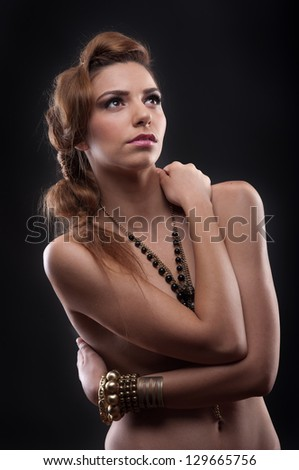 Fashion photo of beautiful nude woman with beads covering her breasts. - stock photo