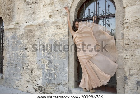 fashion photo of beautiful sensual girl with long dark hair in elegant beige dress posing beside a castle