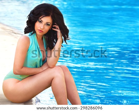 Fashion photo of beautiful sexy brunette model woman with fitness body in swimsuit relaxing at swimming pool. Luxury lifestyle. Blue water background with copy space - stock photo