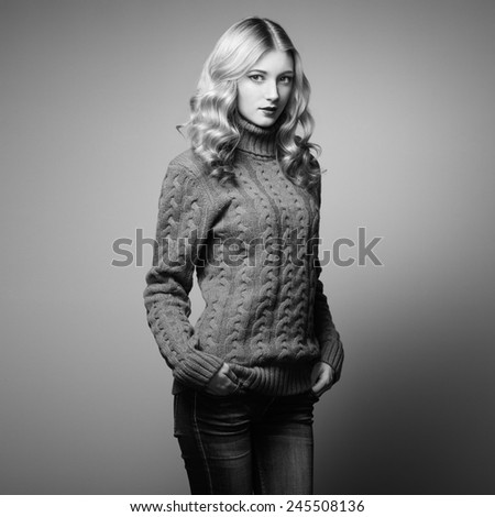 Fashion photo of beautiful woman in sweater. Curly hairstyle. Make-up. Black and white - stock photo