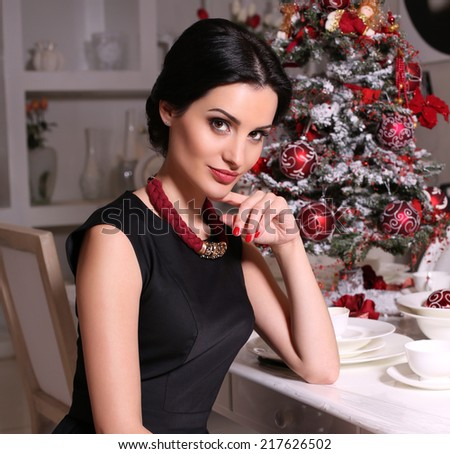 fashion photo of beautiful woman with dark hair in elegant black dress.Christmas tree on background - stock photo
