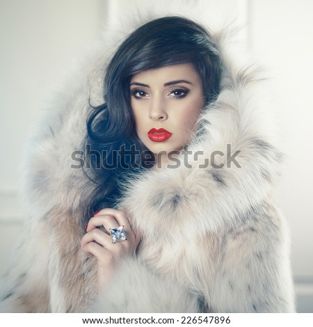 Fashion photo of beautiful young lady in a luxurious fur coat - stock photo