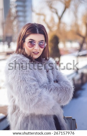 Fashion photo of beautiful young lady in a luxurious fur coat and black lace - stock photo