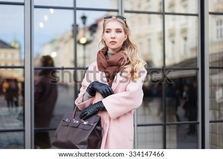 Fashion photo of beautiful young  woman with bag. City lifestyle. Female fashion. Glass reflection background  - stock photo