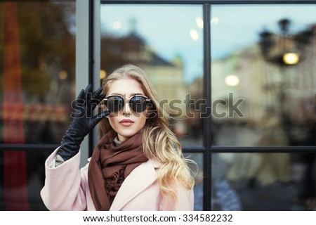 Fashion photo of beautiful young  woman with sunglasses. Model looking at camera. City lifestyle. Female fashion. Closeup portrait. Beautiful reflection background  - stock photo