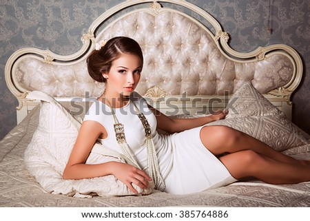 fashion photo of elegant and sexy woman in white clothes,  with beautiful hairstyle posing at bedroom with classic interior - stock photo