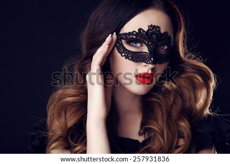 fashion photo of gorgeous woman with dark hair and blue eyes, with lace mask on her face,posing in dark studio  - stock photo