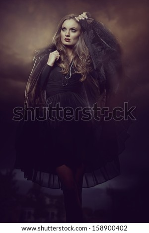 fashion photo of gothic girl in Halloween dress against the dark sky  - stock photo