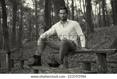 Fashion photo of handsome man in the park - stock photo