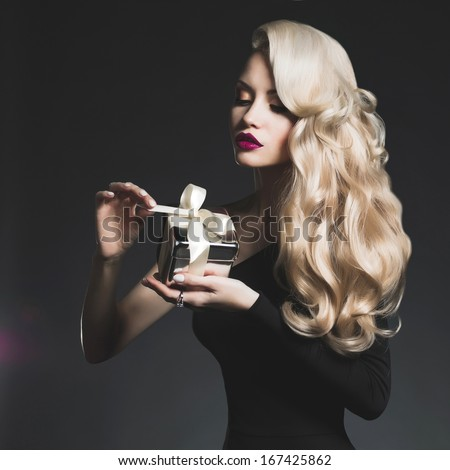 Fashion photo of luxury blonde with a gift - stock photo
