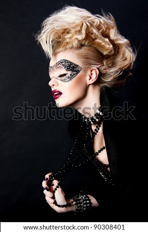 fashion photo of pretty blond woman with mask on face and creative hairstyle - stock photo