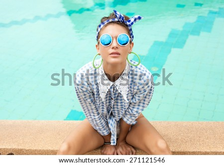 Fashion photo of sexy beautiful Girl in plaid shirt and sunglasses relaxing beside a swimming pool. Outdoors lifestyle  portrait - stock photo