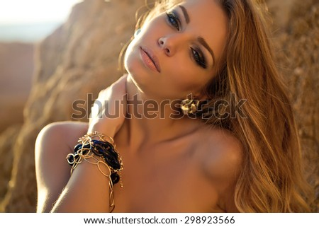 Fashion photo of sexy beautiful girl with blond hair in a black bikini relaxing by the sea. series - stock photo