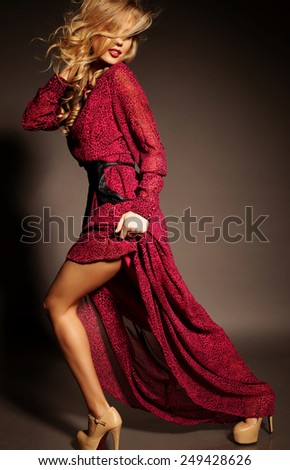 fashion photo of sexy brunette woman in elegant white coat and gold necklace with volume hair and bright evening makeup posing at studio with classic interior - stock photo