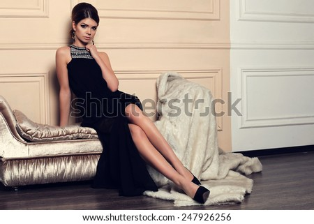 fashion photo of sexy brunette woman in evening black dress,accessories with beautiful hair-dress and long slim legs posing on a bike near the blue door  - stock photo
