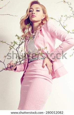 Fashion photo of sexy girl with curly hair wearing a lace dress with pink jacket, earrings and big beautiful necklace,posing at studio around flowering trees - stock photo