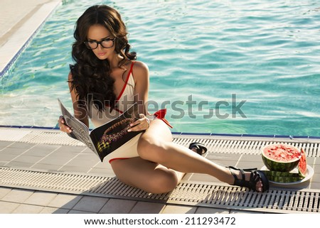 fashion photo of sexy glamour model with dark hair in glasses reading magazine relaxing beside a swimming pool - stock photo