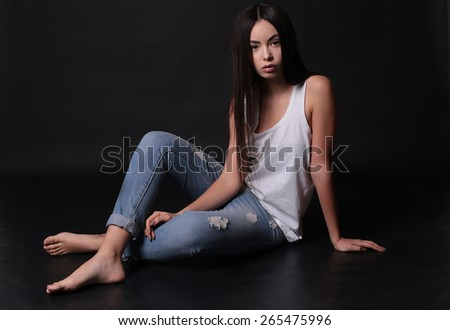 Fashion photo of young beautiful female with brunette long hair, tanned  skin and slim sexy body wearing blue jeans and white top, sitting and posing at studio - stock photo