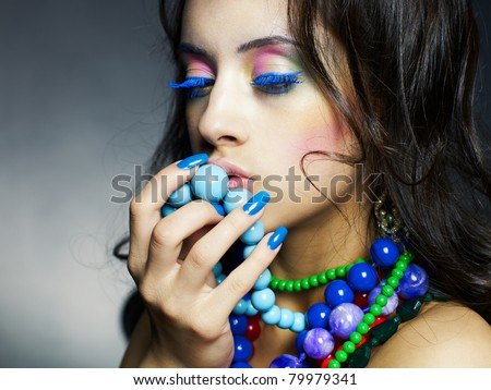 Fashion photo of young beautiful girl with bright beads - stock photo