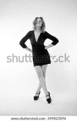 Fashion photo of young lady in elegant black dress on a white background