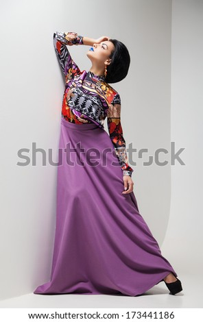 Fashion photo of young magnificent woman in purple dress. Studio photo