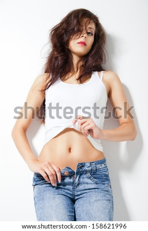 Fashion photo of young sensual woman in jeans over white - stock photo