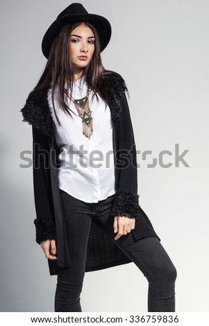 Fashion photo of young woman in trendy cardigan, black jeans and hat. Vintage necklace on the neck.  - stock photo