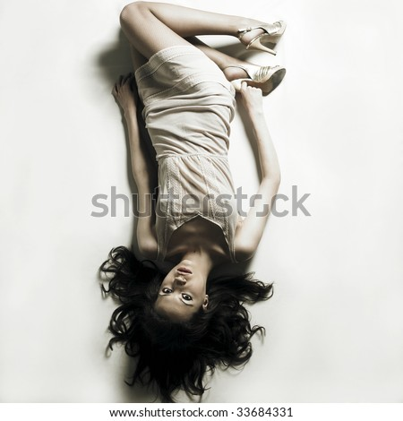 Fashion photo. Young seductive woman lays on white bedsheet - stock photo