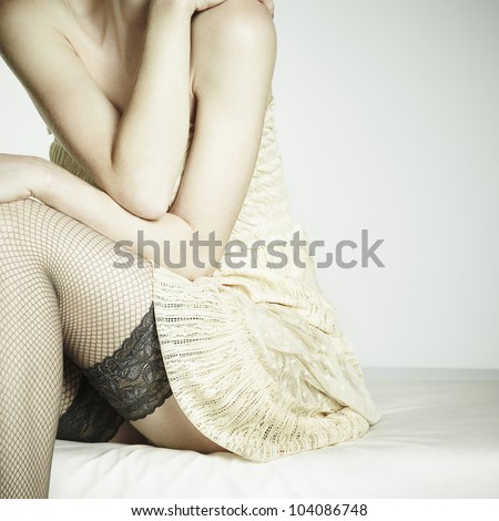 Fashion photo young sexual woman sitting on a sofa. Woman in stockings