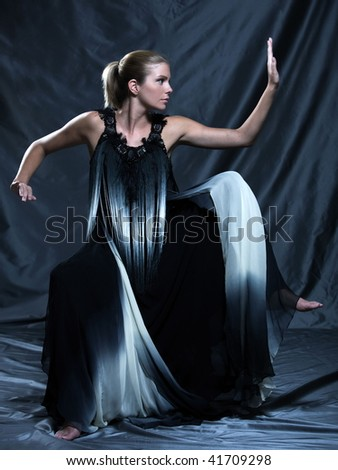 fashion pictures of a beautiful woman wearing silk fringe black and white dress chinese style doing martial arts posture - stock photo