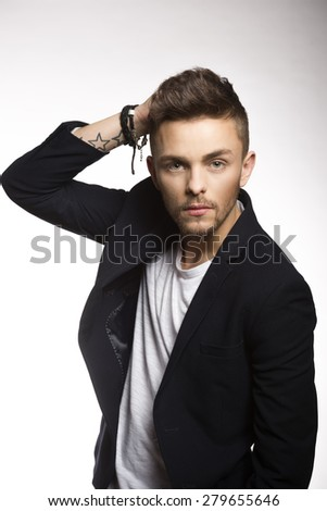 fashion portarit of handsome man , with hair on face , with black jacket and informal pose - stock photo