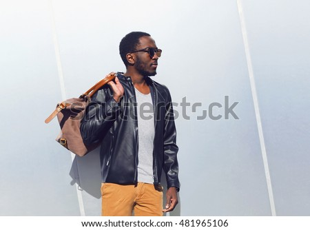 Fashion portrait elegant african man wearing a sunglasses and black rock leather jacket with bag in the city, copy space empty background