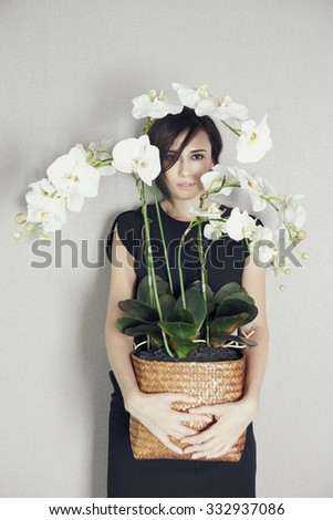 Fashion portrait female model in black dress with orchid - stock photo