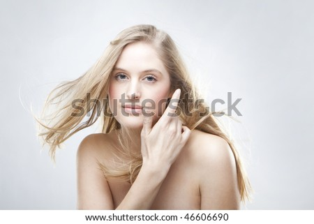 Fashion portrait of a beautiful blonde girl with hair fluttering in the wind - stock photo