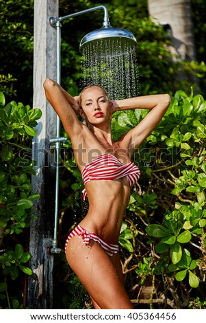 Fashion portrait of a beautiful blonde woman under shower - stock photo