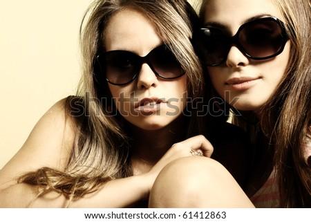 Fashion portrait of a beautiful girls wearing sunglasses - stock photo