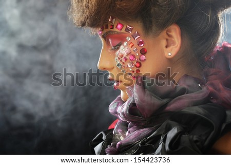 Fashion portrait of a beautiful model with creative make up over dark background - stock photo