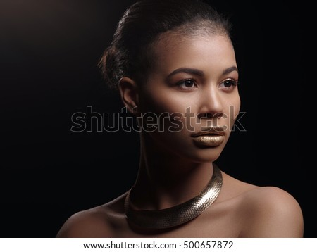 Fashion portrait of a beautiful naked african american woman with perfect smooth glowing mulatto skin, make up, full golden lips, shaved haircut and gold necklace, studio shoot