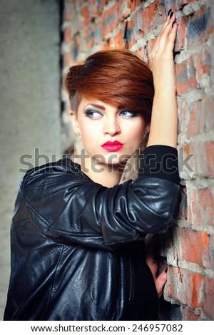 Fashion portrait of a beautiful woman posing near brick wall - stock photo