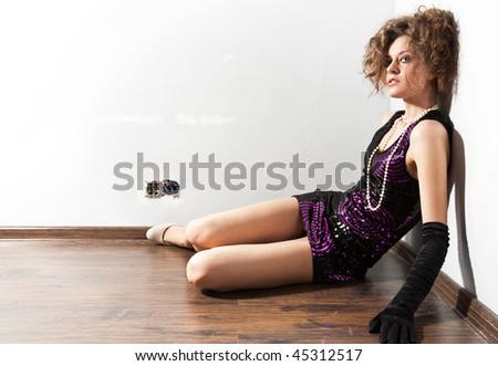 Fashion Portrait of a beautiful young sexy woman sitting on floor - stock photo