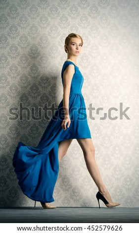 Fashion portrait of a beautiful young woman in  elegant evening dress posing in motion by a vintage wall. Hairstyle. - stock photo