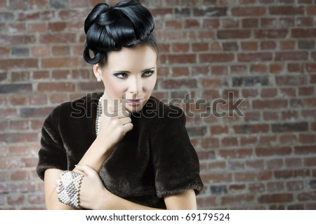 fashion portrait of a cute brunette wearing a brown fur and jewellery near a brick wall - stock photo